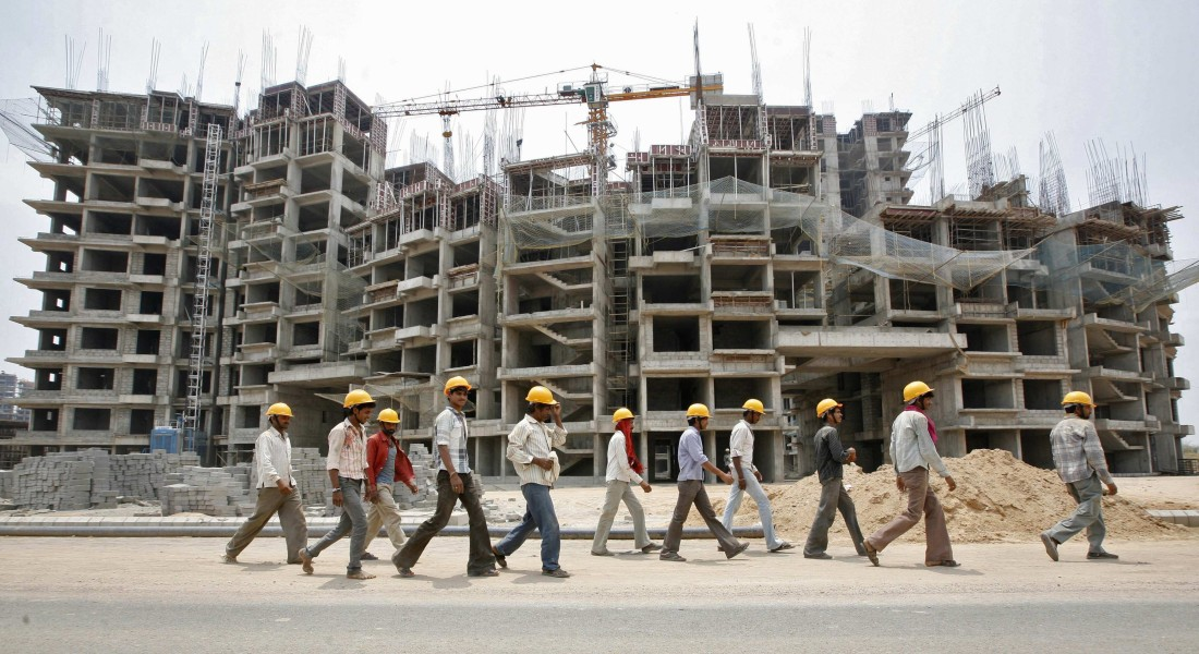 Workers walk in front of the construction site of a commercial complex on the outskirts of the western Indian city of Ahmedabad, in this April 22, 2013 file picture. While India has long suffered from a dearth of workers with vocational skills like plumbers and electricians, efforts to alleviate poverty in poor, rural areas have helped stifle what was once a flood of cheap, unskilled labour from India's poorest states. Struggling to cope with soaring food prices, this dwindling supply of migrant workers are demanding - and increasingly getting - rapid increases in pay and benefits. To match story INDIA-ECONOMY/INFLATION      REUTERS/Amit Dave/Files (INDIA - Tags: BUSINESS CONSTRUCTION EMPLOYMENT TPX IMAGES OF THE DAY)